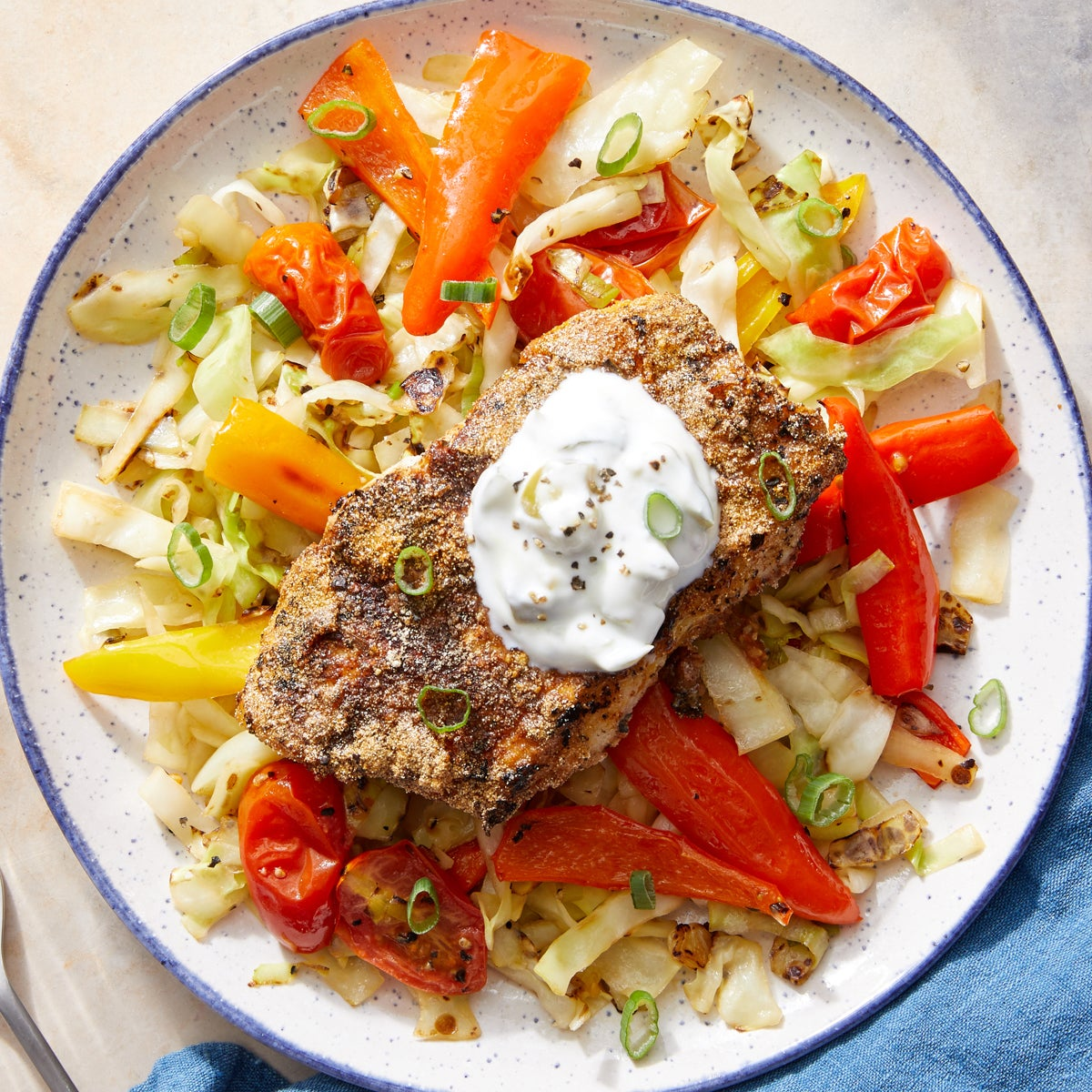 Crispy  Spiced Cod & Jalapeño Yogurt with Sautéed Cabbage, Roasted Peppers & Tomatoes