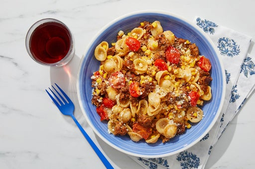 Spicy Pork Sausage Pasta with Corn, Tomatoes & Romano Cheese