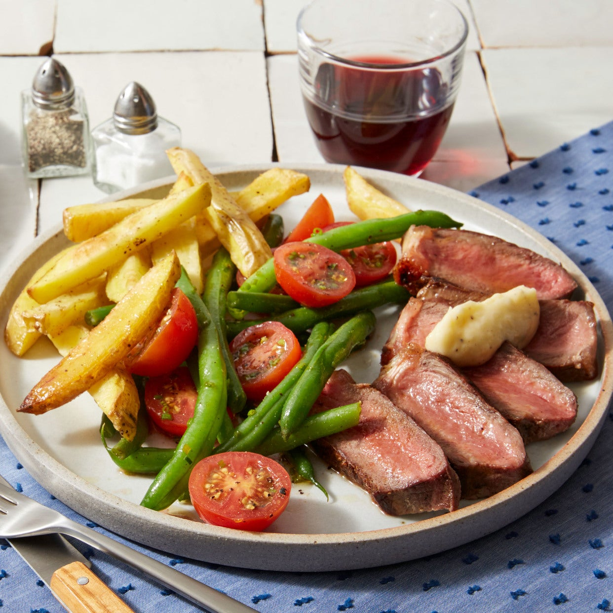 Strip Steaks & Garlic Butter with Oven Fries & Tomato-Green Bean Salad